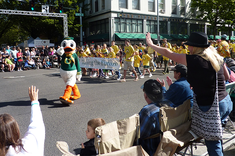 Photo of University of Oregon Duck leading a group of UO students in yellow shirts for a parade while spectators watch, for the CPE Discover page, Community Engagement.