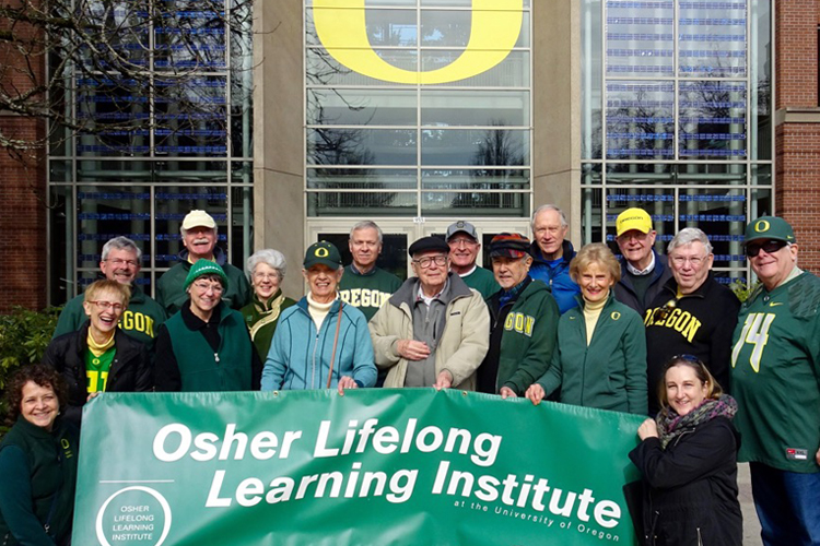 Photo of eleven adults in University of Oregon clothing holding a banner that reads Osher Lifelong Learning Institute in front of UO campus building, for the CPE Discover page, Lifelong Learning section.