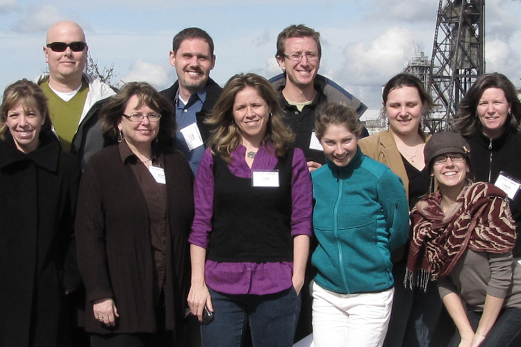 Photo featuring nine professional development students posing with a bridge visible in the background, for the CPE Discover page, Professional Development.