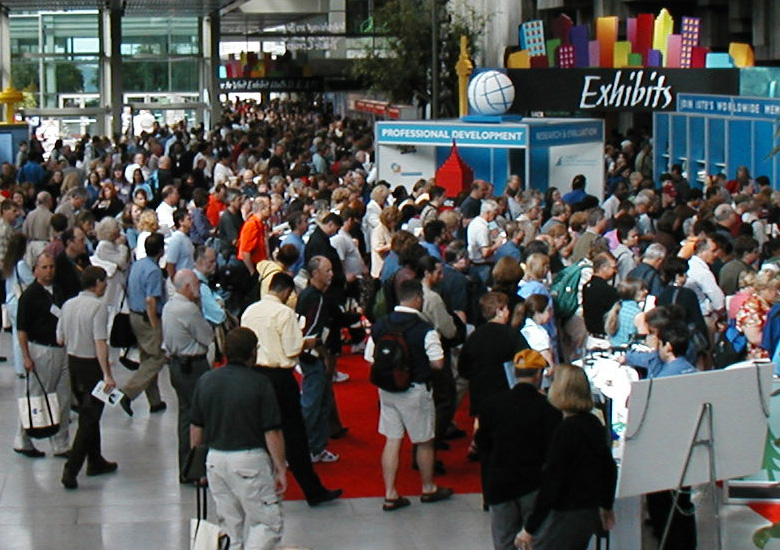 Photo of a large conference hall with hundreds of people walking through to their conference, for the CPE homepage.