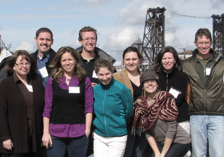 Photo featuring nine professional development students posing with a bridge visible in the background, for the CPE homepage.