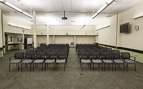 Large open classroom with several rows of chairs in lecture style seating for Eugene Event Facilities page.