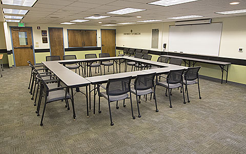 Small classroom with tables and chairs positioned in a square for Eugene Event Facilities page.